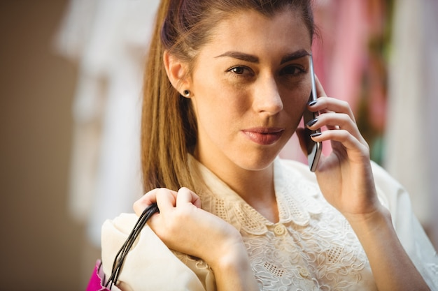 Woman talking on mobile phone while shopping Free Photo