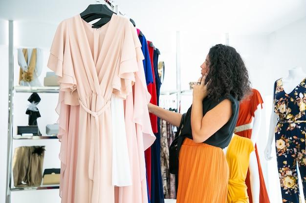 옷을 선택하고 패션 매장에서 선반에 드레스를 검색하는 동안 셀에 얘기하는 여자. 중간 샷, 측면보기. 부티크 고객 또는 소매 개념 무료 사진