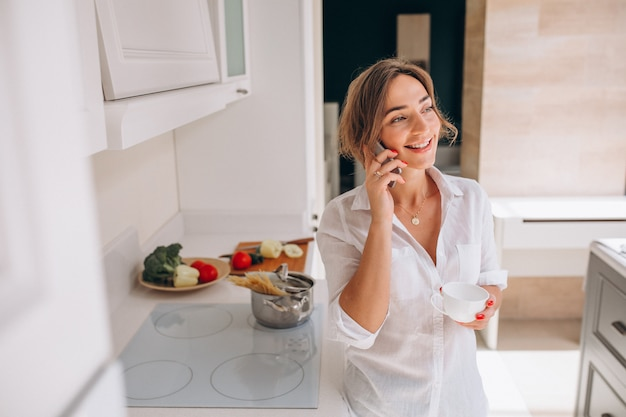 Woman talking on the phone at kitchen and cooking breakfast Free Photo