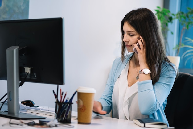 Woman talking on phone in office Free Photo