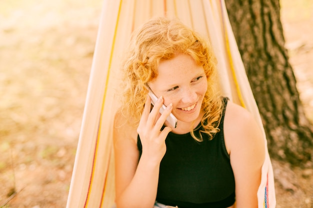 Woman talking on phone outdoors Free Photo