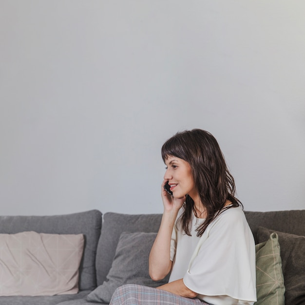 Woman talking on phone sitting on couch Free Photo