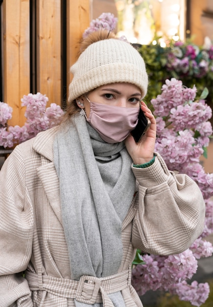 Donna che parla al telefono mentre indossa la mascherina medica Foto Gratuite