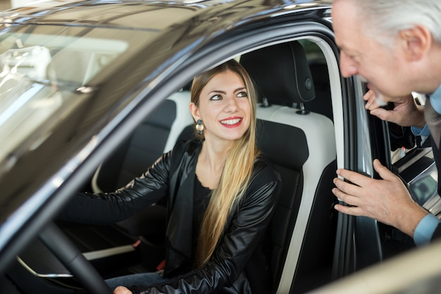 Woman talking to the salesman to buy her new car in a showroom Premium Photo