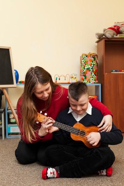 Женщина учит мальчика с синдромом дауна играть на гитаре Бесплатные Фотографии