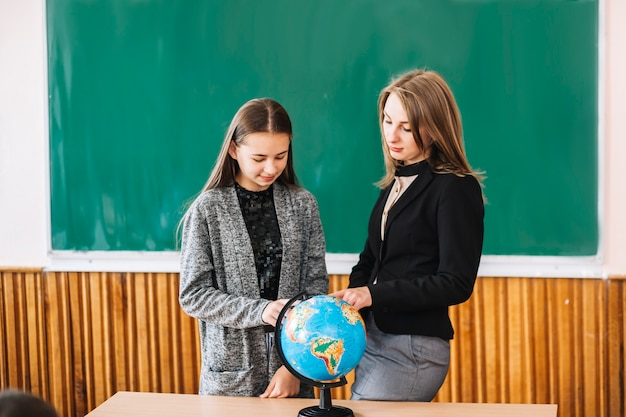 Woman teaching geography to student girl Free Photo
