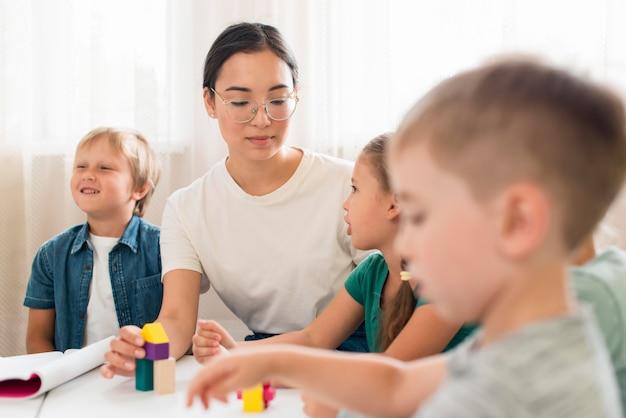 カラフルなゲームで遊ぶ方法を子供たちに教える女性 無料写真