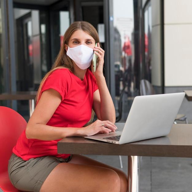 Donna in terrazza con maschera Foto Gratuite