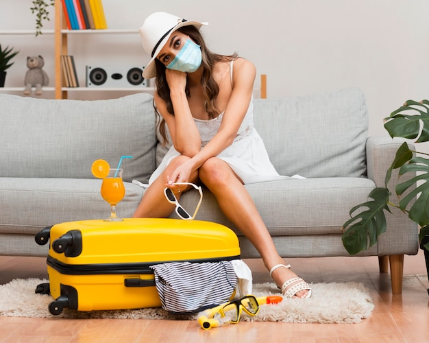 Woman thinking about her postponed holiday while wearing a medical mask Premium Photo