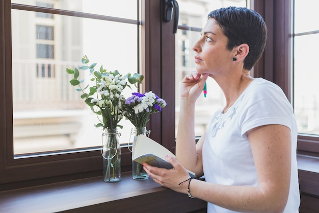 Woman thinking and looking through the window Free Photo