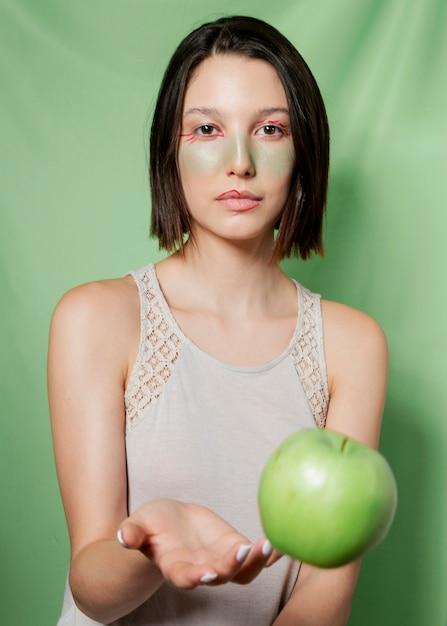 Woman throwing apple while posing Free Photo