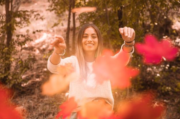 Женщина бросает осенние листья в камеру Бесплатные Фотографии