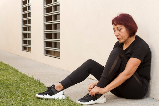 Woman ties the laces outdoors Free Photo