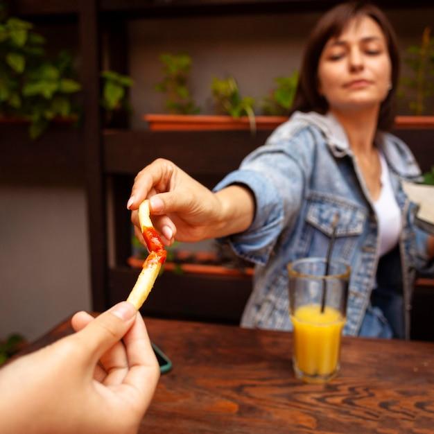 Donna che tosta con la sua amica utilizzando patatine fritte con ketchup Foto Gratuite