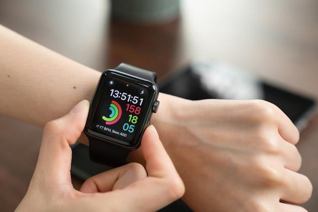 時計に触れる女性。多くの機能に使用できるデジタル時計。 Premium写真