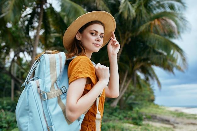 女性観光バックパック旅行散歩エキゾチックなヤシの木熱帯 Premium写真