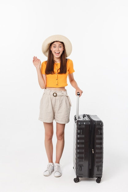 Woman tourist. full length happy young woman standing with suitcase with exciting gesturing, isolated on white wall. Premium Photo
