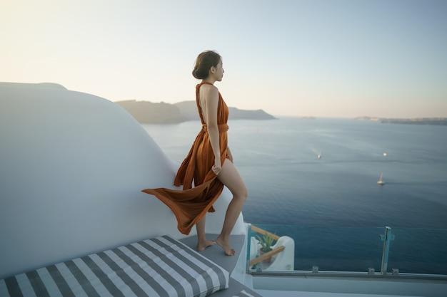 ギリシャのイアサントリーニ島の白塗りの村を訪れるゴージャスなドレスを着た女性観光客 Premium写真