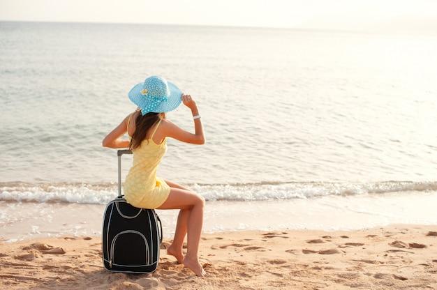 Woman tourist sitting near the sea on suitcase Premium Photo