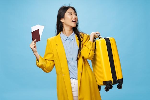 休暇旅行パスポートと空港の女性観光スーツケース Premium写真