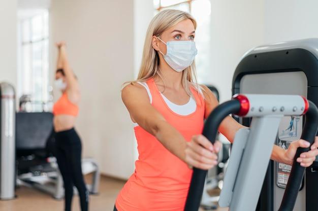 Женщина тренируется в тренажерном зале с маской Бесплатные Фотографии