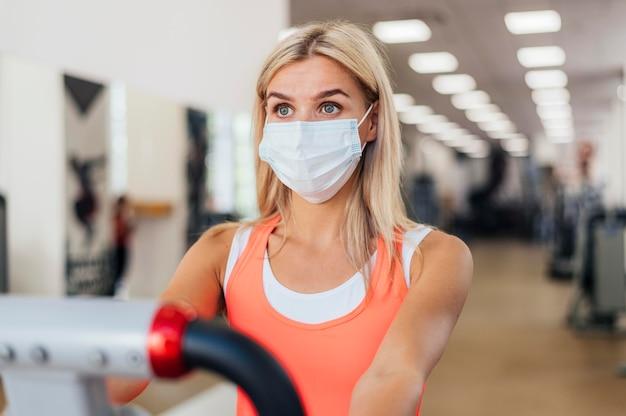 Женщина тренируется в тренажерном зале с медицинской маской Бесплатные Фотографии