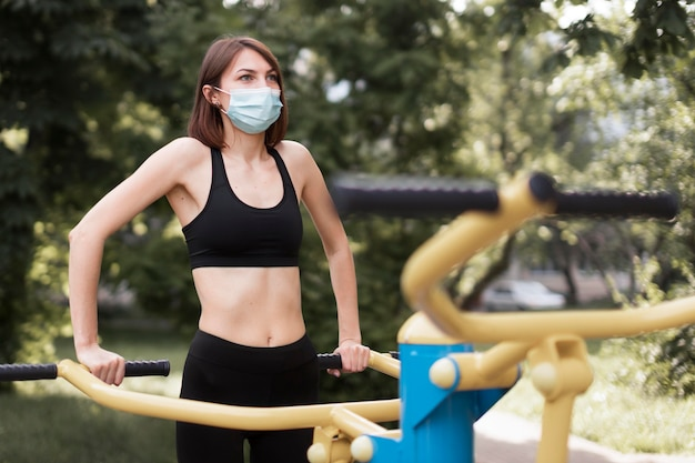 Woman training for her next sports event while wearing a medical mask Premium Photo
