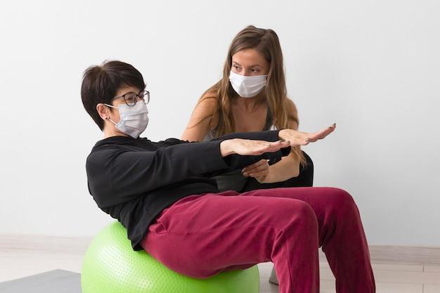 Женщина тренируется на фитнес-мяче в медицинской маске Бесплатные Фотографии