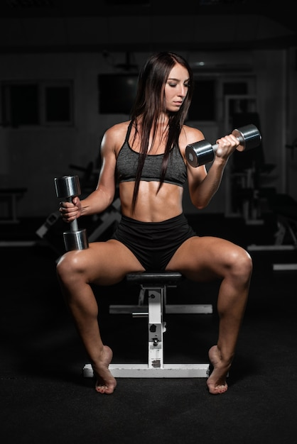 Woman trains in the gym. athletic woman trains with dumbbells, pumping her biceps Premium Photo