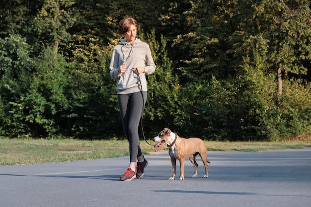 Женщина тренирует свою собаку бегать во время пробежки. молодая подтянутая сука и стаффордширский терьер на утренней прогулке, делая физические упражнения Premium Фотографии