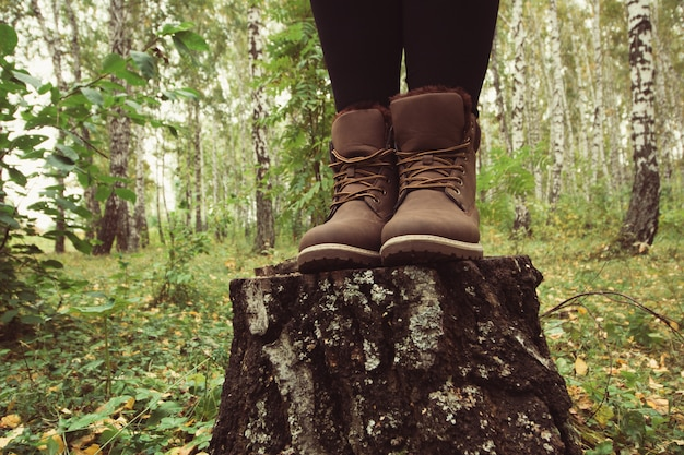 Woman traveler legs in leather brown boots in forest Premium Photo