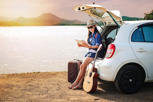 Woman traveler sitting on hatchback of car and looking at map near the lake Premium Photo