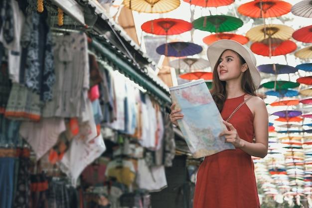 Woman traveler tourist with map traveling on walking street. journey trip travel Premium Photo