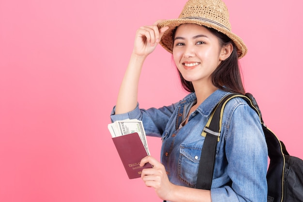 Woman traveler wearing straw hat is holding passport with banknote Free Photo