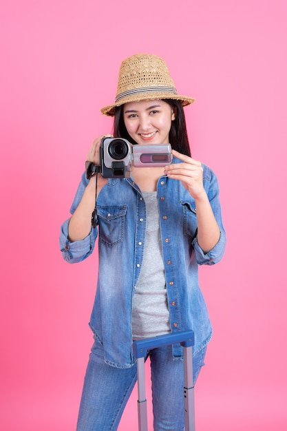 Woman traveler wearing traw hat is holding video recorder, portrait of pretty smiling happy teenager on pink Free Photo