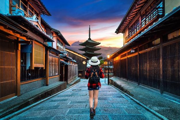 Путешественница с рюкзаком гуляет по пагоде ясака и улице саннен зака в киото, япония. Бесплатные Фотографии
