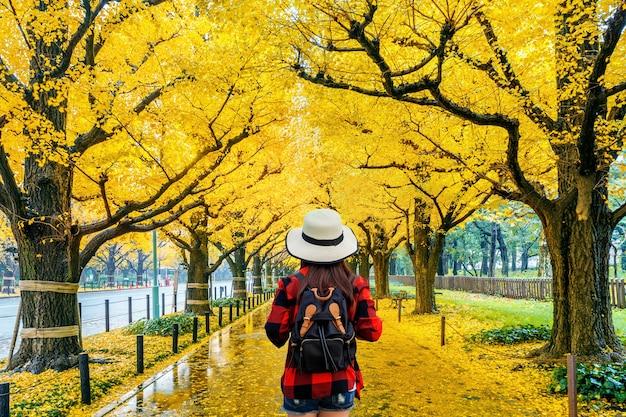 가 노란 은행 나무의 행에 걷는 배낭 여성 여행자. 일본 도쿄의 가을 공원. 무료 사진
