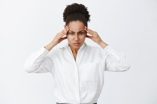 Donna che cerca di concentrarsi, cerca soluzioni nel cervello, essendo un grande stratega. ritratto di intensa imprenditrice cercando di concentrarsi, accigliato, tenendo le mani sulle tempie, pensando a fatica a trovare una soluzione Foto Gratuite