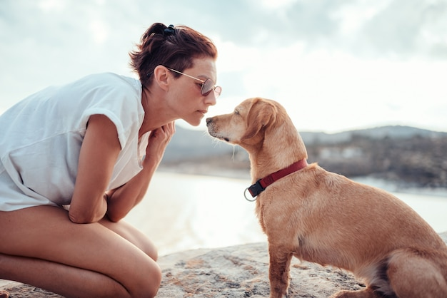 Woman trying to make eye contact with her dog on the beach Premium Photo