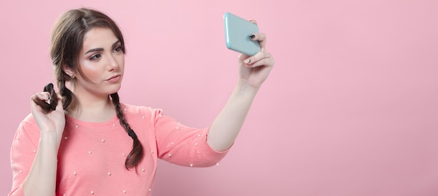 Woman trying out poses for selfie while holding smartphone Free Photo