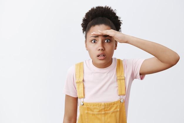 Donna che prova a vedere attraverso la nebbia malata. ritratto di preoccupato e confuso attraente afroamericano in salopette gialla, tenendo il palmo vicino alla fronte e guardando lontano, in piedi sopra il muro grigio Foto Gratuite