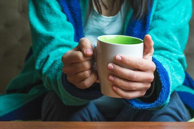 Donna in abiti turchesi che tiene una tazza di tè Foto Gratuite