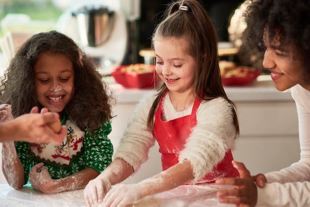 Donna e due ragazze che preparano i biscotti di natale Foto Gratuite