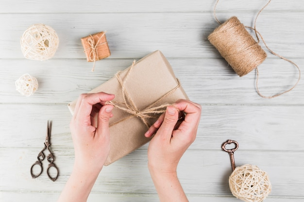 Donna che lega il contenitore di regalo con corda sulla superficie di legno strutturata Foto Gratuite