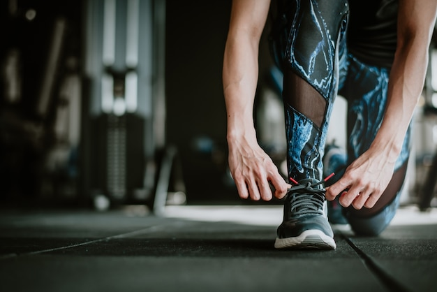 Woman tying her shoelaces before exercise Premium Photo