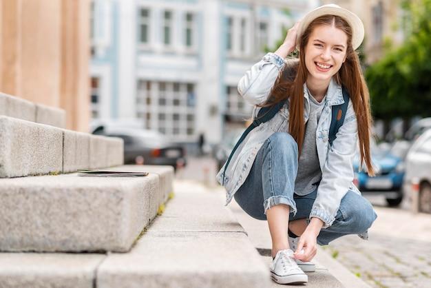 建物の隣で彼女の靴を結ぶ女 無料写真
