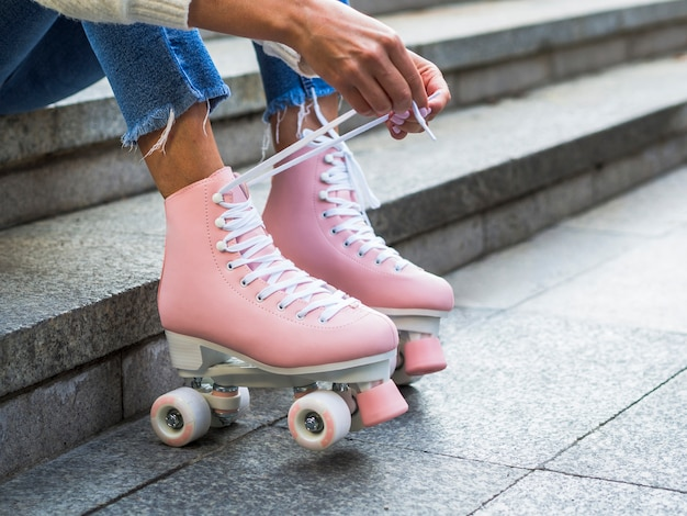 Woman tying shoelaces on roller skates with copy space Free Photo