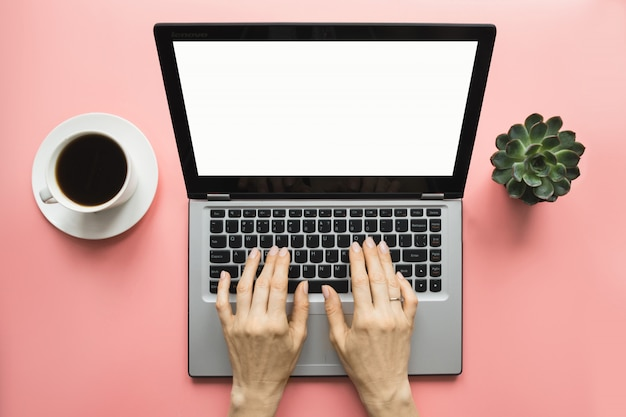 Woman typing by laptop on office pink table. space for text on screen. Premium Photo