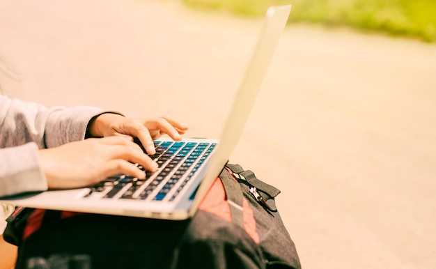Woman typing on laptop placed on backpacks Free Photo