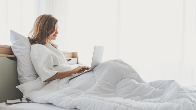 Woman typing work laptop on bed working in bedroom at home Premium Photo